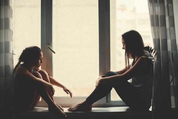 Twee jonge tienermeisjes met een mok thee denken, zittend op de vensterbank.