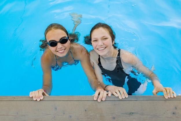 Twee jonge tienermeisjes met plezier in het zwembad.