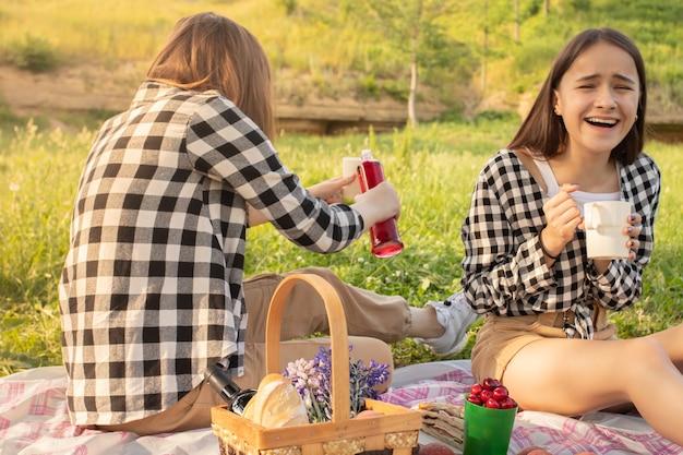Twee jonge tienermeisjes op een picknick eten, limonade drinken, plezier maken, lachen, praten