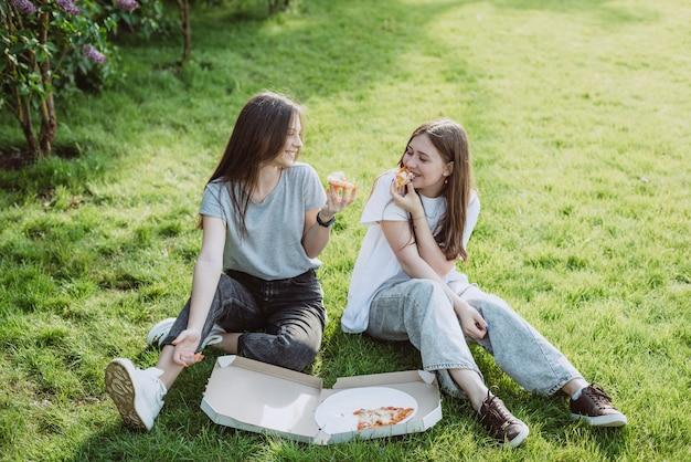 Twee jonge tienervrienden die plezier hebben in het park op het gras en pizza eten. vrouwen eten fastfood. geen gezond dieet. zachte selectieve focus.