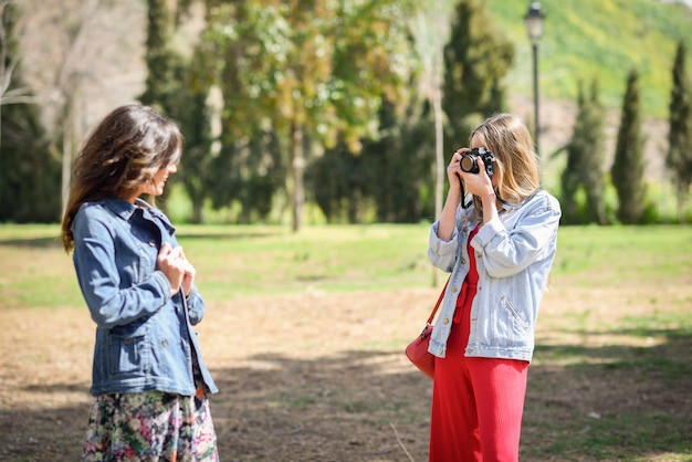 Twee jonge toeristenvrouwen die foto's met analoge reflexcamera in stedelijk park nemen.