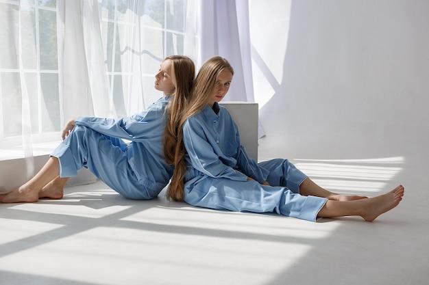 Twee jonge tweelingmeisjes in identieke blauwe pakken zittend op witte cyclorama vloer in de studio