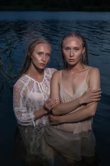 Twee jonge tweelingzusjes met lang blond haar poseren in lichte jurken in het water van het meer op zomeravond