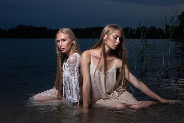 Twee jonge tweelingzusjes met lang blond haar poseren in lichte jurken in het water van het meer 's nachts