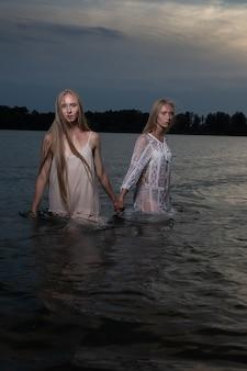 Twee jonge tweelingzusjes poseren in lichte jurken in het water van het meer op zomernacht