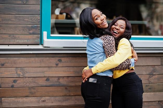Twee jonge universiteits afrikaanse amerikaanse vrouwenvrienden omhelzen elkaar.