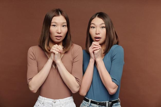 Twee jonge verbaasde brunette vrouwtjes van aziatische etniciteit houden handen bij elkaar en gekruist door kinnen terwijl ze grote verbazing uitdrukken