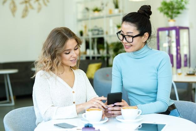 Twee jonge, vriendelijke vrouwen in vrijetijdskleding bespreken goederen uit de online winkel terwijl ze op hun gemak iets nieuws uitkiezen