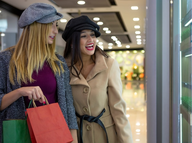 Twee jonge vrienden blonde en brunette kijken naar een etalage in het winkelcentrum op een winkeldag