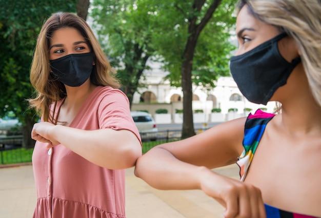 Twee jonge vrienden die een gezichtsmasker dragen en tegen hun ellebogen stoten om hallo te zeggen terwijl ze buiten staan