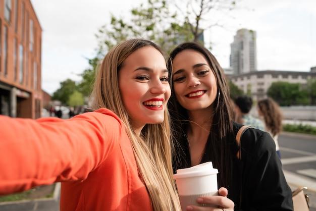 Twee jonge vrienden die een selfie in openlucht nemen.