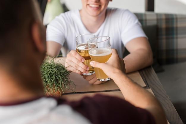 Twee jonge vrienden die glazen bier roosteren