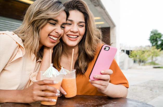 Twee jonge vrienden die hun mobiele telefoon gebruiken en vers vruchtensap drinken bij een koffieshop buiten