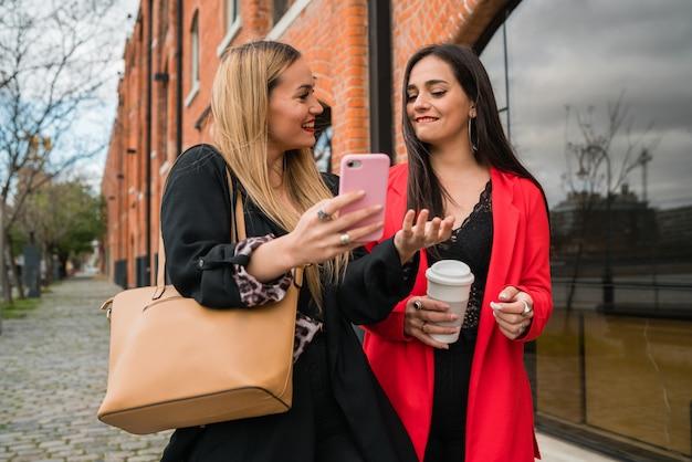 Twee jonge vrienden die hun mobiele telefoon in openlucht gebruiken.