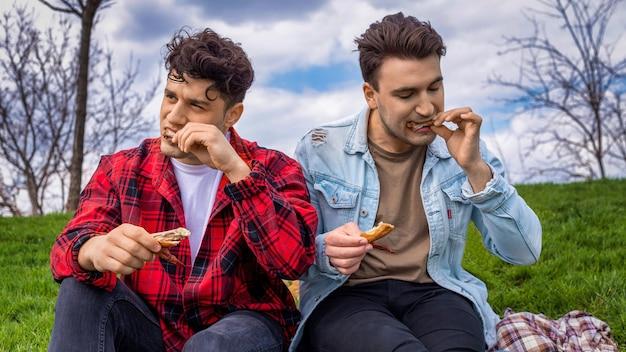 Twee jonge vrienden die kip eten in een park
