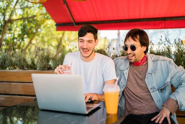 Twee jonge vrienden die laptop met behulp van bij koffiewinkel.