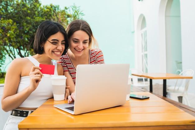 Twee jonge vrienden die winkel online doen