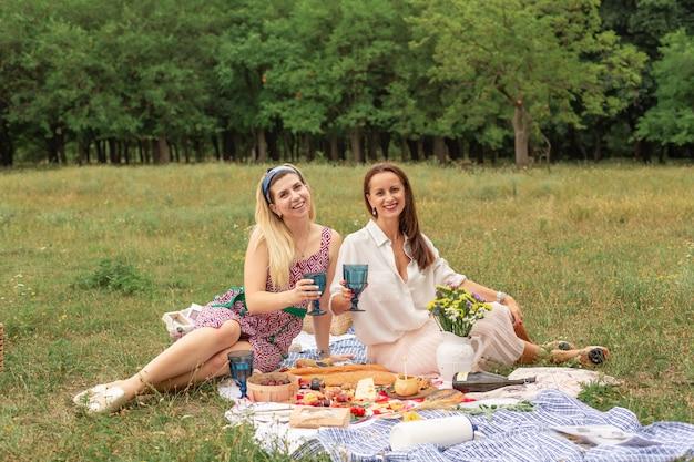 Twee jonge vrienden genieten van openluchtpicknick