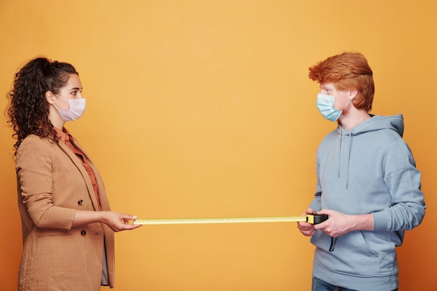 Twee jonge vrienden in vrijetijdskleding en beschermende maskers staan voor elkaar en meten twee meter tussen hen in