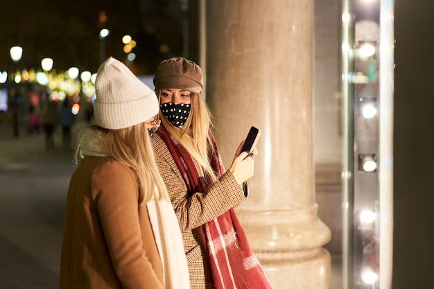 Twee jonge vrienden kijken in een etalage, in een stad 's nachts. een van hen laat haar vriendin iets zien op haar smartphone.