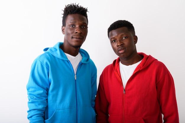Twee jonge vrienden tegen witte muur