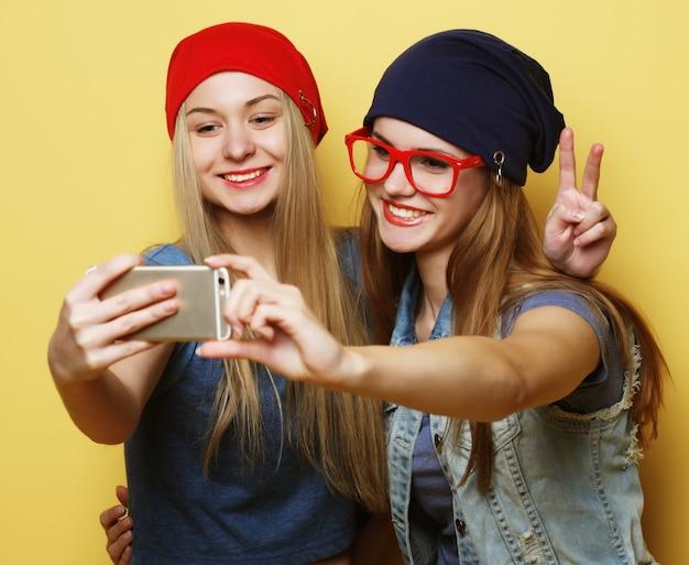 Twee jonge vrienden van hipstermeisjes die selfie op geel nemen