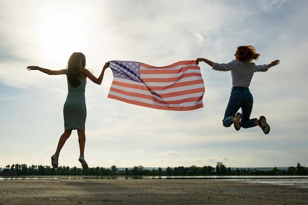 Twee jonge vriendenvrouwen die de nationale vlag houden die van de vs samen in openlucht omhoog springen bij zonsondergang. silhouet van meisjes die de onafhankelijkheidsdag van verenigde staten vieren.