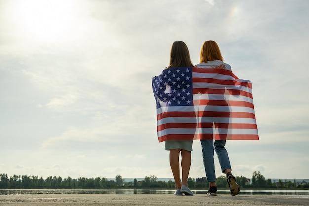 Twee jonge vriendenvrouwen met de nationale vlag van de v.s. op hun schouders die samen staan