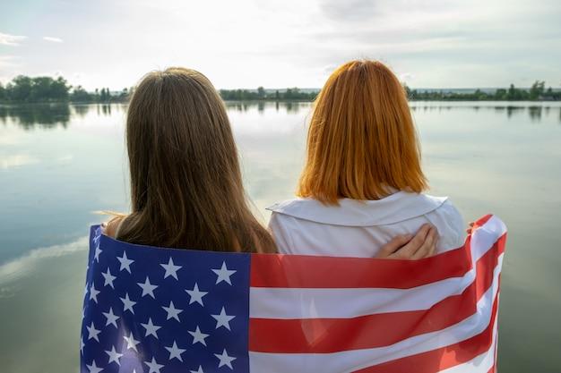 Twee jonge vriendenvrouwen met de nationale vlag van de vs op hun schouders die zich in openlucht op meerkust verenigen.