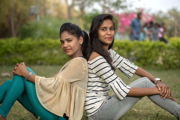Twee jonge vriendinnen die samen plezier hebben in de buitenlucht. kijkend naar de camera.