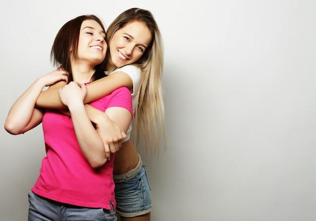 Twee jonge vriendinnen die zich verenigen en pret hebben. kijkend naar de camera.