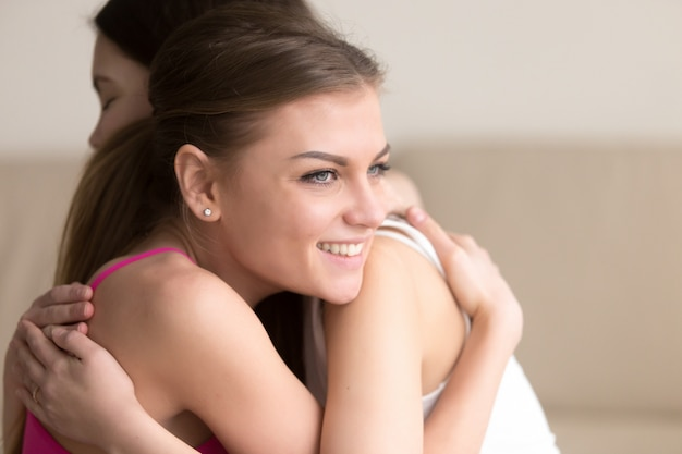 Twee jonge vriendinnen omhelzen elkaar, meisje glimlachend gelukkig