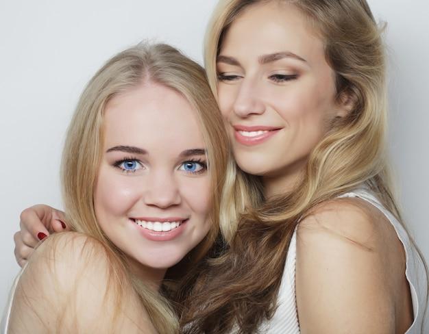 Twee jonge vriendinnen staan samen en hebben plezier. camera kijken.