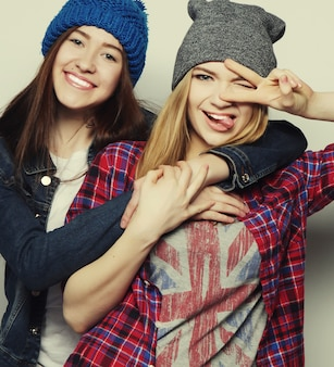 Twee jonge vriendinnen staan samen en hebben plezier. tekenen met handen tonen. camera kijken
