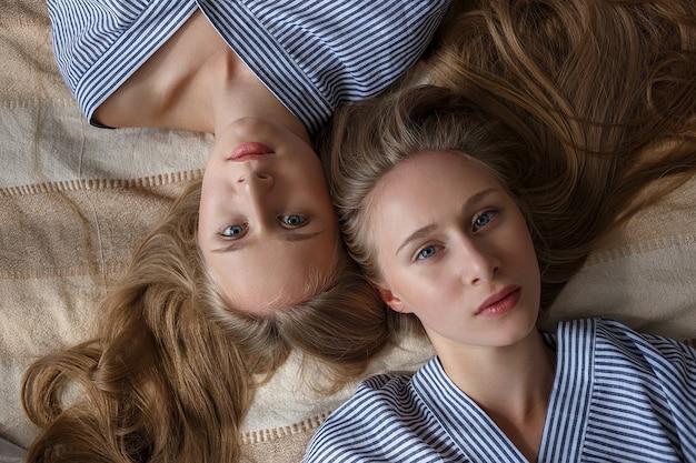 Twee jonge vrij kaukasische tweelingzusters in gestreepte overmaatse overhemden die op bank liggen