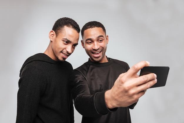 Twee jonge vrolijke afrikaanse mannen maken een selfie.