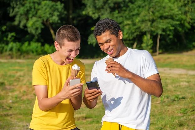 Twee jonge vrolijke en lachende afro-amerikaanse en blanke vrienden eten ijs en gebruiken smartphone, maken selfie terwijl ze in de zomer buiten in het park staan
