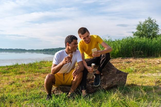Twee jonge vrolijke en lachende afro-amerikaanse en blanke vrienden eten ijs en gebruiken smartphone, maken selfie terwijl ze in de zomer buiten op het strand van de rivier zitten