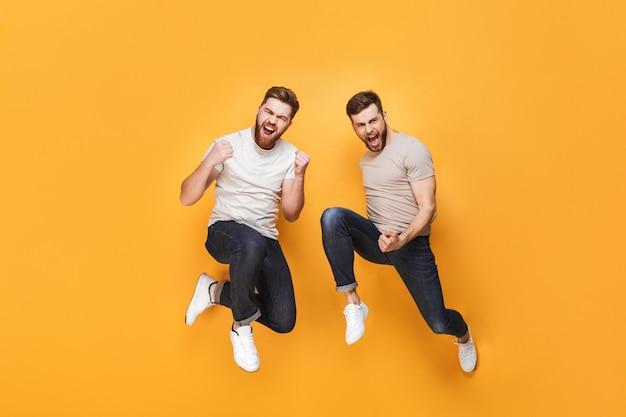 Twee jonge vrolijke mannen die samen springen