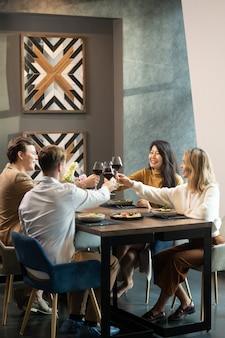 Twee jonge, vrolijke, vriendelijke stellen in slimme vrijetijdskleding die met glazen rode wijn rammelen aan tafel bij het diner in restaurant