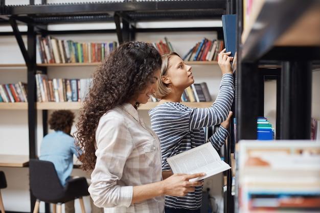 Twee jonge vrolijke vrouwelijke studenten in vrijetijdskleding die zich dichtbij boekenrekken in universiteitsbibliotheek bevinden die door literatuur voor teamproject kijken