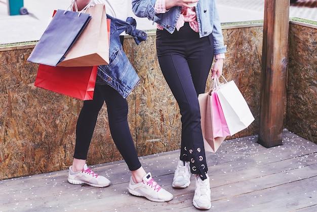 Twee jonge vrouw met boodschappentassen tijdens het wandelen in de straat na een bezoek aan de winkels.