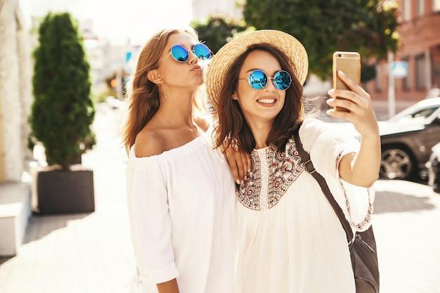 Twee jonge vrouwelijke glimlachende modellen van hippie donkerbruine en blonde vrouwen in kleding van de zomer de witte hipster die selfie foto's voor sociale media op telefoon nemen. verras gezicht, emoties,