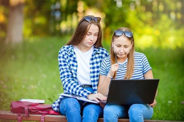 Twee jonge vrouwelijke meisjes zitten in de zomer op een bankje in het park met een laptop en smartphone. concept van werken op afstand, freelancen, online afstandsonderwijs en onderwijs.