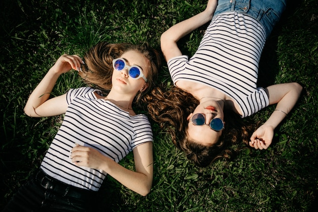 Twee jonge vrouwelijke meisjesvrienden die in zonnebril op het gras in park leggen
