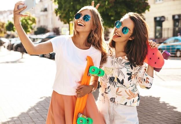 Twee jonge vrouwelijke stijlvolle hippie brunette en blonde vrouwen modellen in zomer hipster kleding nemen selfie foto's voor sociale media op de telefoon. met kleurrijke penny skateboards.