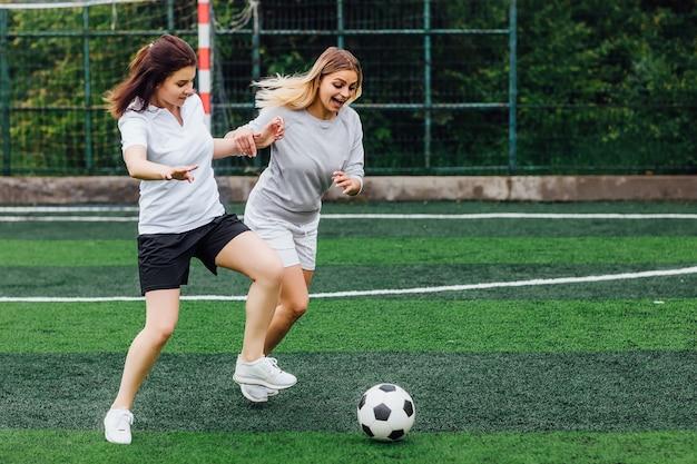 Twee jonge vrouwelijke voetballers op het veld