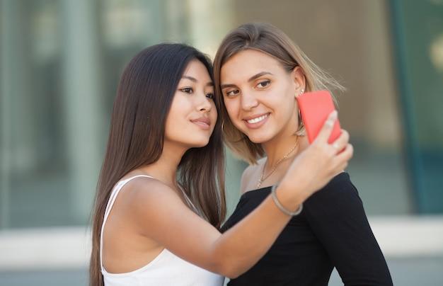 Twee jonge vrouwelijke vrienden die een foto van zichzelf op een slimme telefoon.