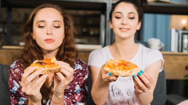 Twee jonge vrouwelijke vrienden die pizzaplak houden