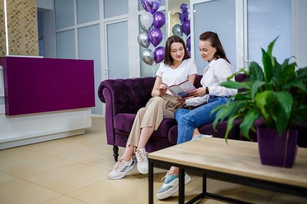 Twee jonge vrouwelijke vriendinnen zitten op de bank en praten. vrouwvriendelijke chat